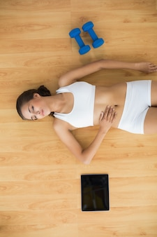 Sporty woman with closed eyes lying next to a tablet and dumbbells