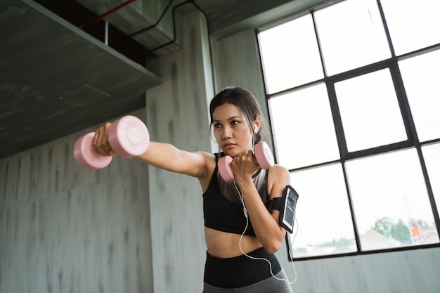 Sporty woman with dumbbell doing weight exercise