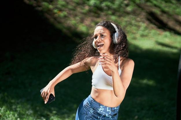 도시 공원에서 헤드폰 춤을 추는 스포티 한 여자