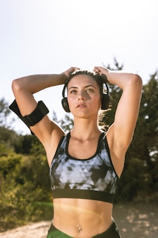Sporty woman with headphones getting ready to run