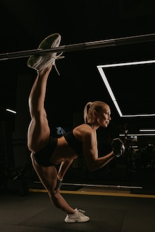 A sporty woman with long blonde hair is doing a twine during dumbbell bicep curls in a gym. a girl is stretching.