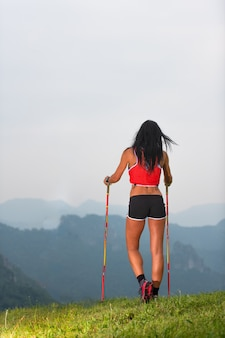 Sporty woman with nice body looks at the panorama in the mountains during on trekking
