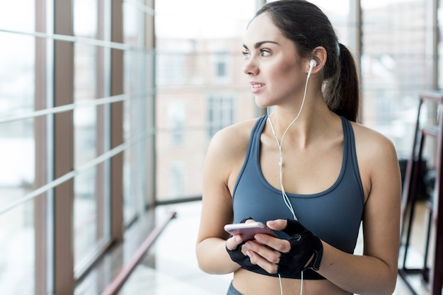 Sporty woman with phone looking away