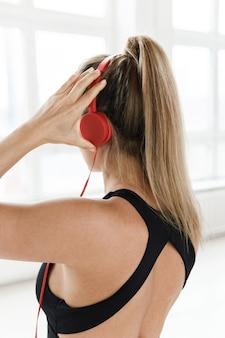 ジムでのトレーニングのためにやる気を起こさせる音楽を聞いている赤いヘッドフォンでスポーティな女性