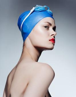 水泳トレーニングの感情のための赤い唇のキャップを持つスポーティな女性