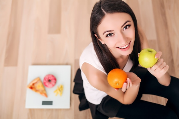 Sporty woman with scale and green apple and orange