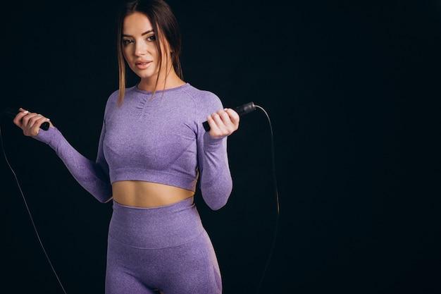 Donna sportiva con corda per saltare isolata su sfondo nero