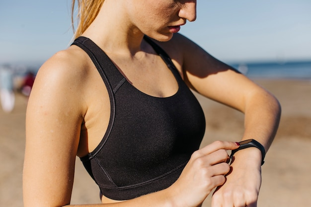 Sporty woman with smartwatch at the beach