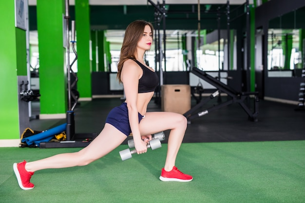 Sporty woman with strong fit body is doing different exercises in modern sportclub with mirrors