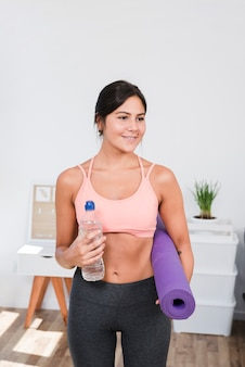 Sporty woman with yoga mat