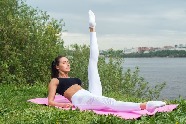 スポーティな女性の腹筋腹筋フィットネスの彼女の強さでワークアウトし、屋外で痩身