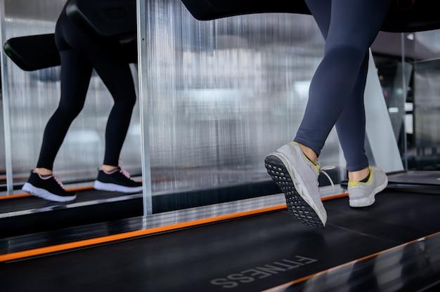 スポーティな女性のトレーニングとマシンのトレッドミルで実行しています。フィットネスジムでのアジアの女性の運動とライフスタイル。ボディービルのための健康と健康。