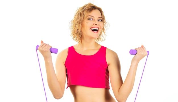 Спортивная тренировка женщины с прыжками через скакалку. улыбающийся фитнес-инструктор со скакалкой. фитнес, активность, спортивный образ жизни.
