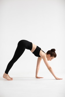 Sporty yoga girl on white background stretching in pose adho mukha svanasana, downward-facing dog pose, downward dog, down dog. concept of healthy life and natural balance. full length