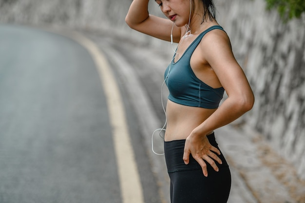 Sporty young asian woman tired sport exercises, wipes sweat from her face.she standing on the road. fitness ,workout, gym exercise ,lifestyle and healthy concept.