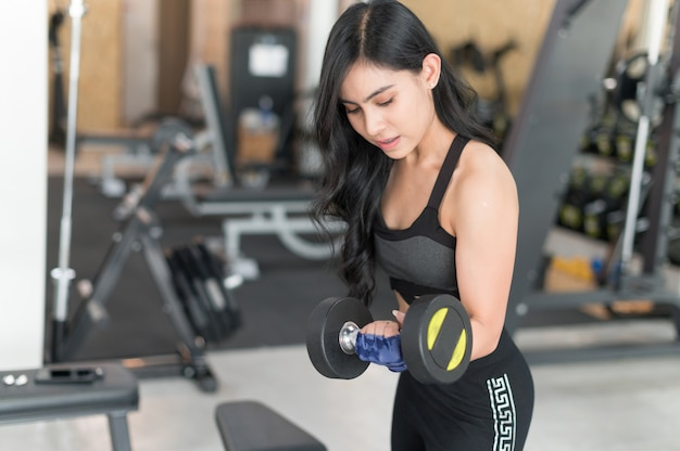 Sporty young asian woman with dumbbell