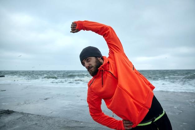 スポーティな若い黒髪のひげを生やした男性、黒い帽子と暖かい運動オレンジ色のコートで筋肉を伸ばし、朝のトレーニングの準備をしています。スポーツと健康的なライフスタイルのコンセプト