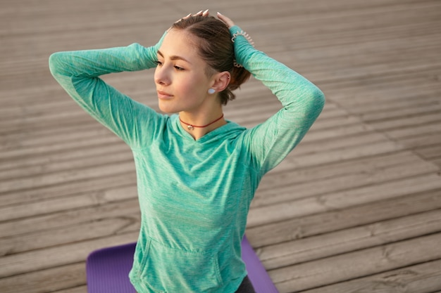 Sporty young female sits in yoga pose, dressed in bright sportwears, trains at the seaside, calming and meditate.