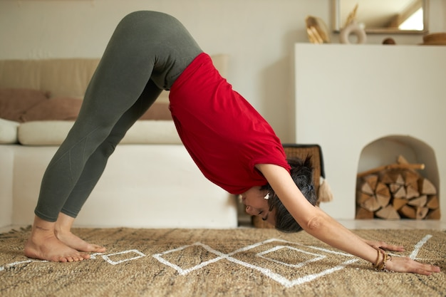 Sporty young female in sportswear standing in downward facing dog pose