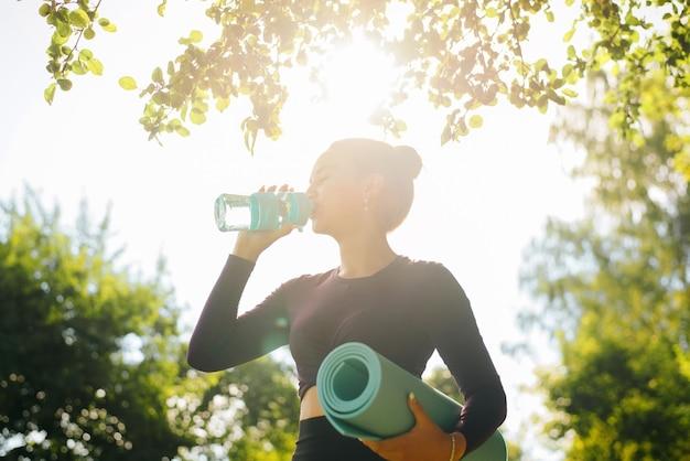 운동복을 입은 스포티한 젊은 여성은 피트니스 병에서 물을 마시고 요가 매트, 나뭇잎 틀에 초상화를 들고 있습니다. 야외에서 맑은 하늘을 배경으로 스포츠우먼을 마시는 실루엣.