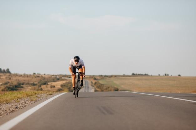 스포티 한 젊은 남자가 포장 도로에서 빨리 자전거를 타는 활동복을 입고 있습니다.