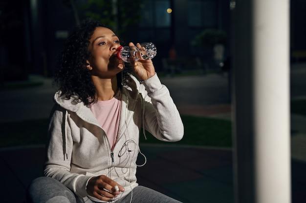 木製のベンチに座っているボトルから水を飲むスポーティな若いヒスパニック系女性