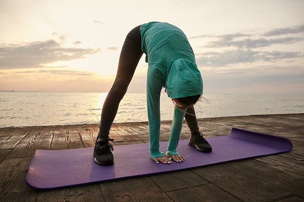 Sporty young lady wears in bright sportswear, makes morning stretching on the purple yoga mat, trains at the seaside.