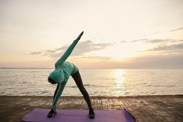 Спортивная барышня носит яркую спортивную одежду, делает утренние упражнения на растяжку на берегу моря.