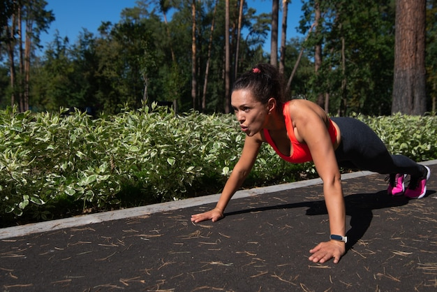 Sporty young latin americanwoman doing push-ups outdoor. push-ups exercises outdoor