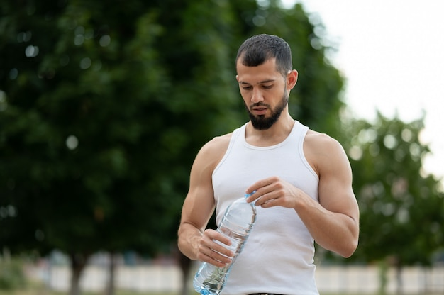 夏に公園で水を飲むスポーティな若い男