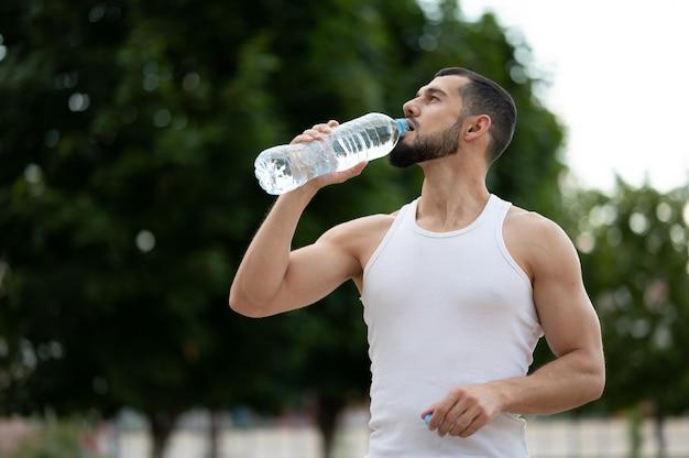 公園で水を飲むスポーティな若い男