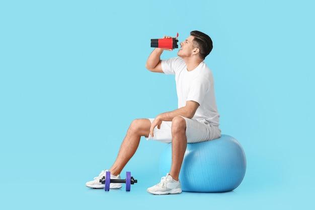 Спортивный молодой человек пьет воду на цветной поверхности