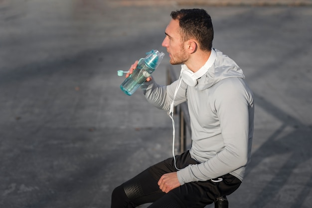 Sporty young man drinking water