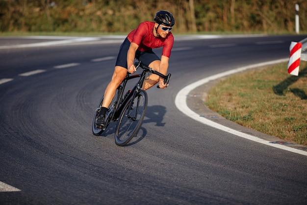 검은 헬멧, 미러 안경 및 아스팔트 도로에서 자전거를 타는 활동복에 스포티 한 젊은 남자