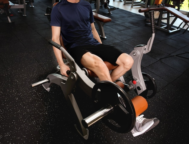 체육관에서 스포티 한 젊은 남자 훈련 다리