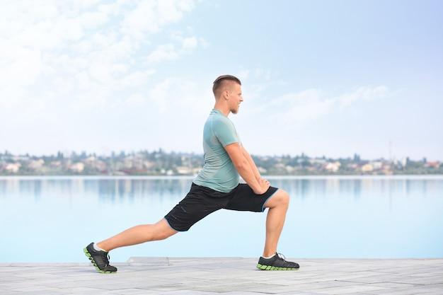 川の近くで屋外でトレーニングするスポーティな若い男