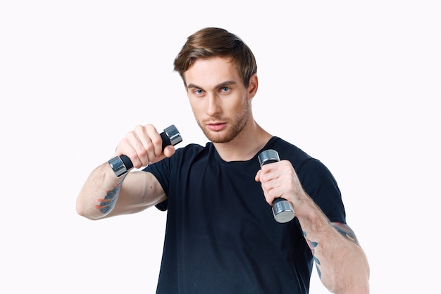 Sporty young man with dumbbells on white background workout copy space