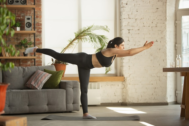 Sporty young muslim woman taking yoga lessons online and practice at home