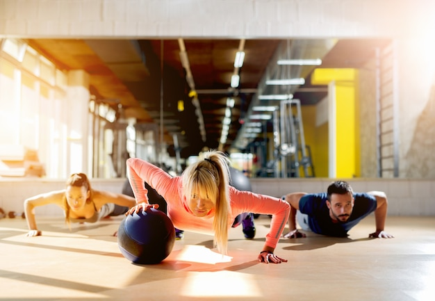 Sporty young people doing pushups at gym looking focused