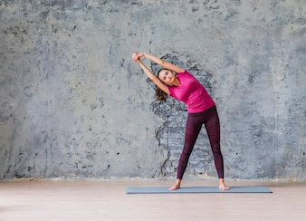 Sporty young woman doing fitness exercise standing against grey wall
