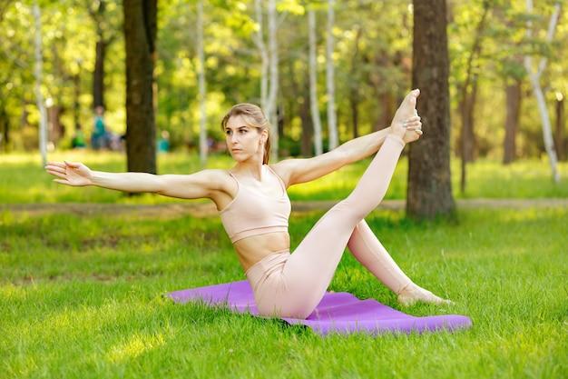 공원에서 여름 날에 필라테스 연습을 하 고 스포티 한 젊은 여자.