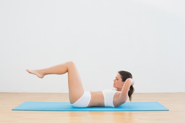 Sporty young woman doing sits up at fitness studio