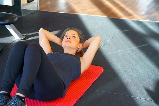Sporty young woman doing sits-up at gym