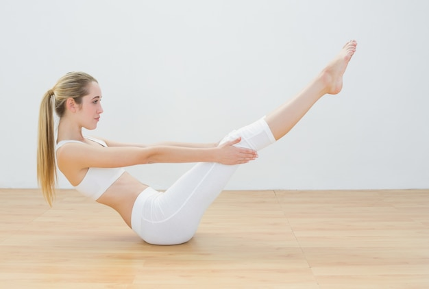Sporty young woman doing sports exercise sitting on floor