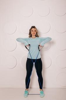 Спортивная молодая женщина делает утреннюю зарядку на корточках в одиночестве в гостиной, серьезная подтянутая девушка в спортивной одежде, приседая, тренирует мышцы дома для концепции здорового образа жизни, вид сбоку
