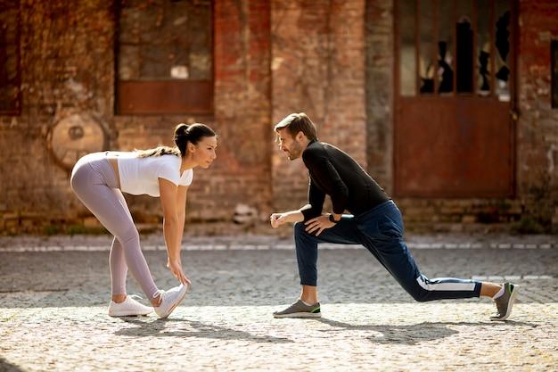 Спортивная молодая женщина делает упражнения на растяжку после пробежки со своим личным тренером