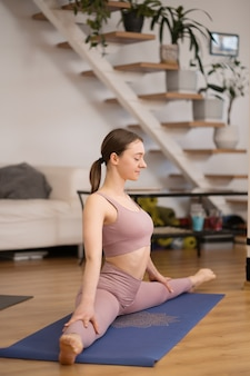 건강한 삶과 신체와 정신 발달 사이의 자연 균형의 개념-스트레칭 연습을 하 고 스포티 한 젊은 여자, 문자열 포즈