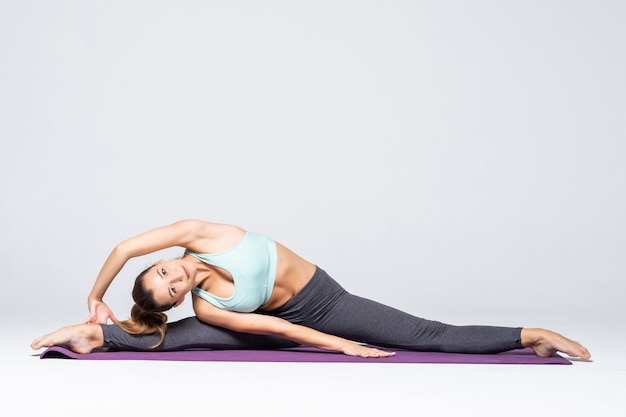 Sporty young woman doing yoga practice isolated. concept of healthy life and natural balance between body and mental development. full length