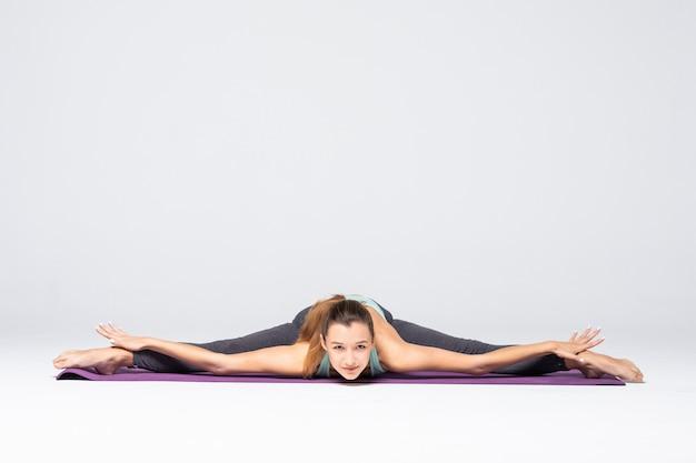 고립 된 요가 연습을 하 고 스포티 한 젊은 여자. 건강한 삶의 개념과 신체와 정신 발달 사이의 자연스러운 균형. 전체 길이