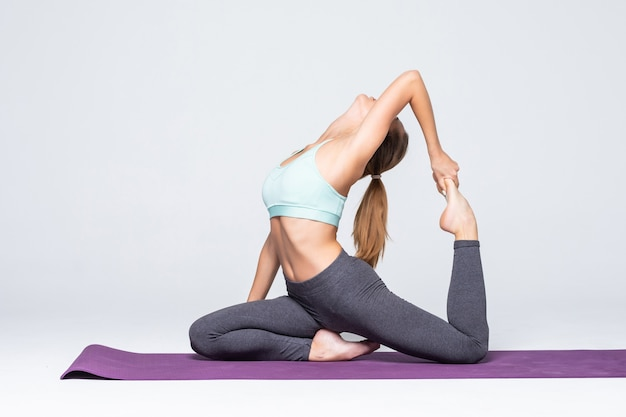 孤立したヨガの練習をしているスポーティな若い女性-健康的な生活と体と精神の発達の間の自然なバランスの概念